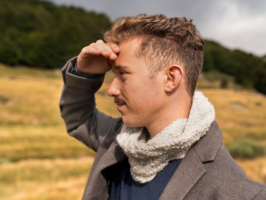 Man wearing knitted scarf facing a brown field