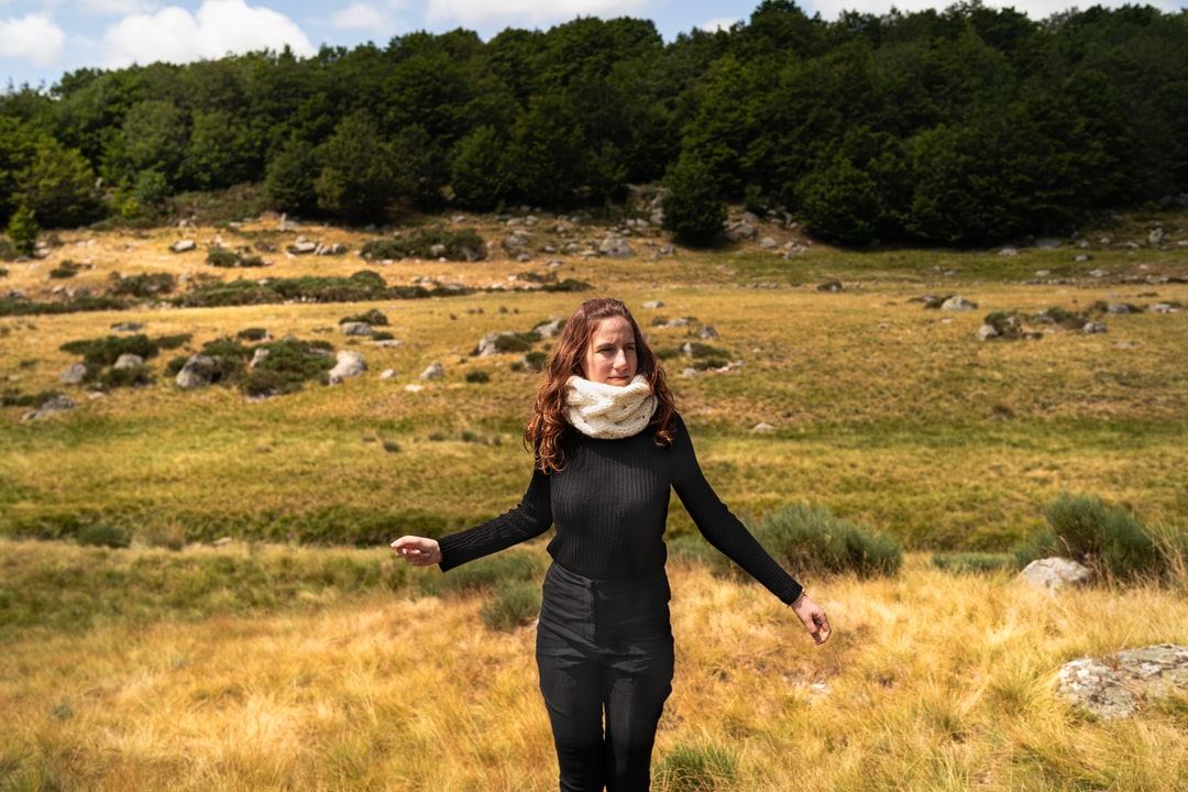 Woman stand on brown field wearing black clothes and white knitted scarf