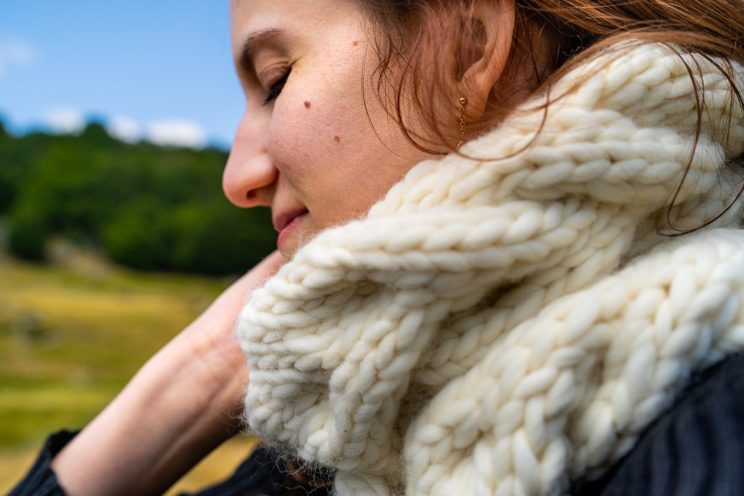 Woman wearing knitted scarf with cables