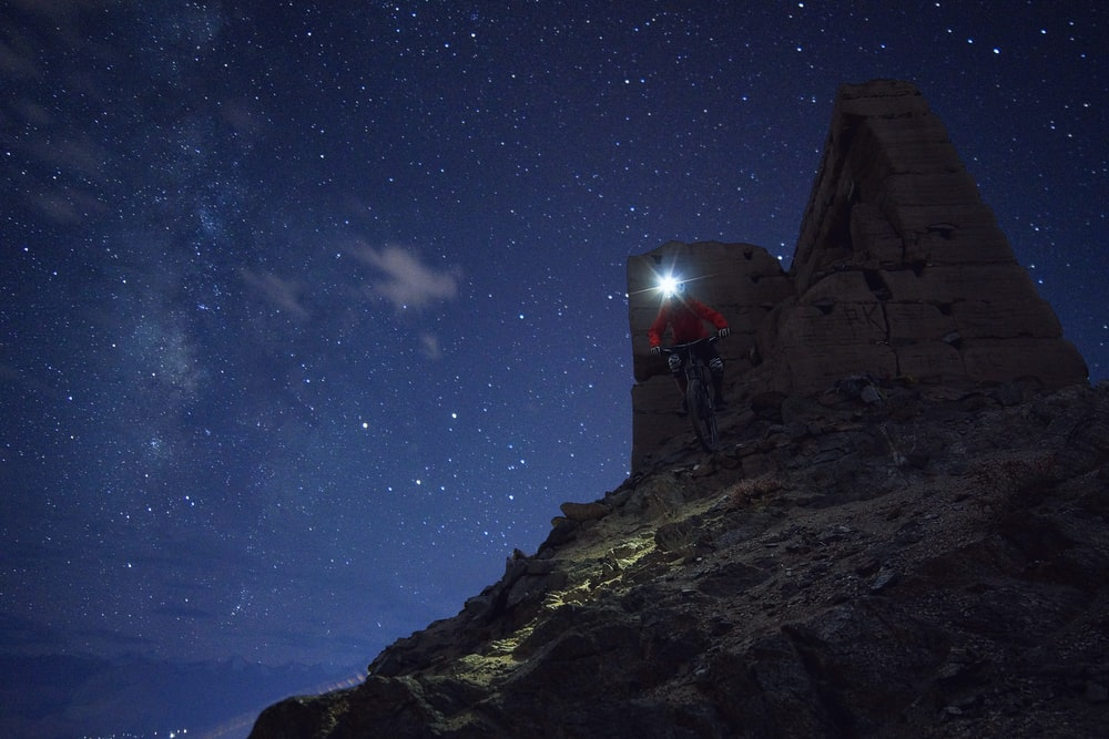 man riding on bicycle with headlamp on head on rock formation