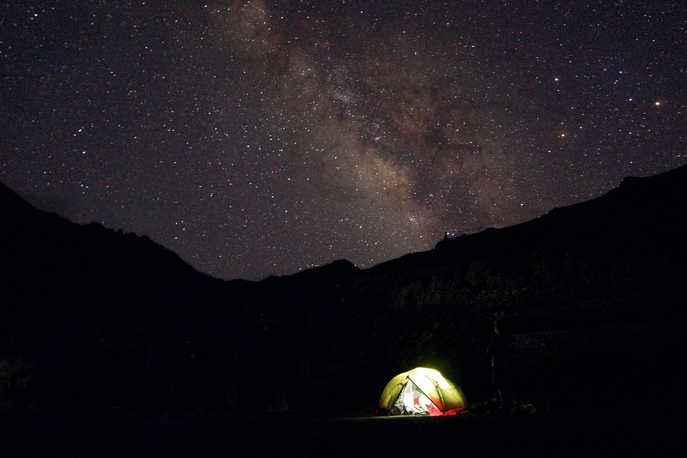 green tent with turned-on light in front of silhouette of mountain under the galaxy