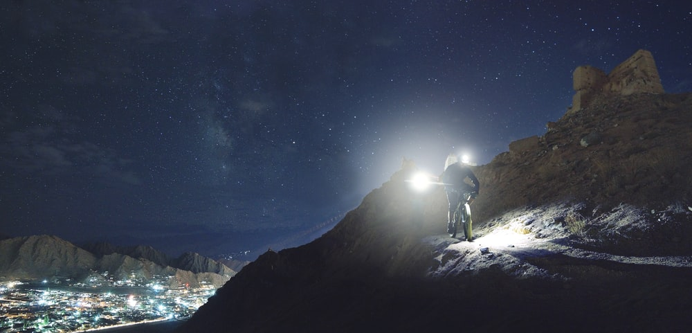 man holding turned-on flashlight standing on the cliff