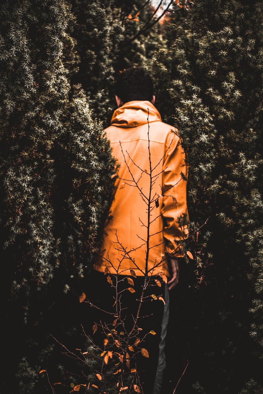 man in orange jacket near trees