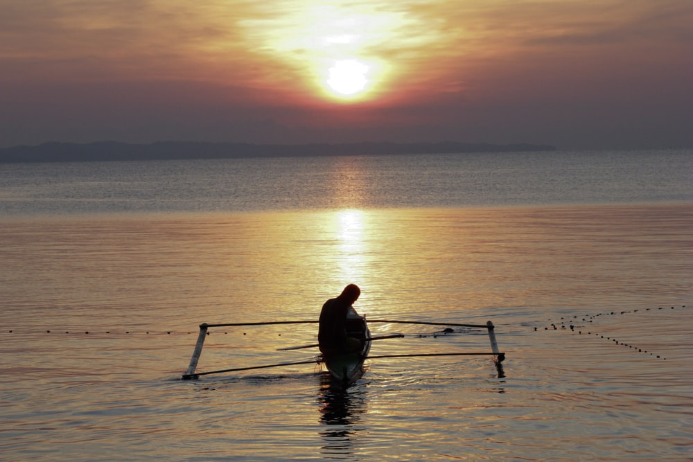 silhouette of man riding boat on calm body of water