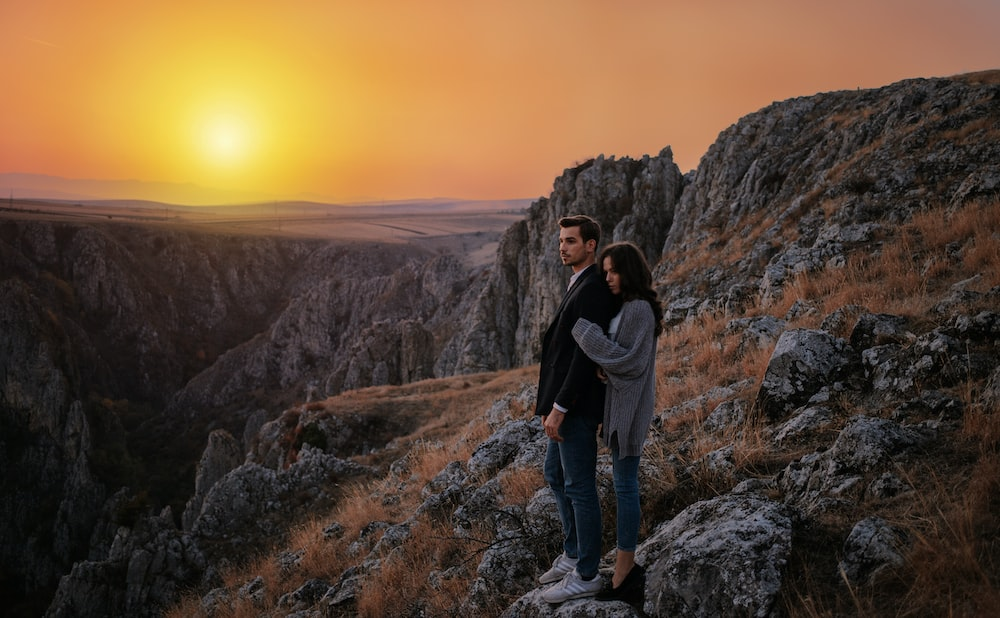 man and woman standing on boulder during golden hour