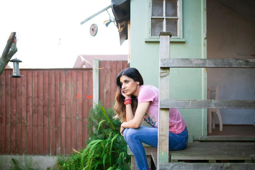 woman sitting beside green wall