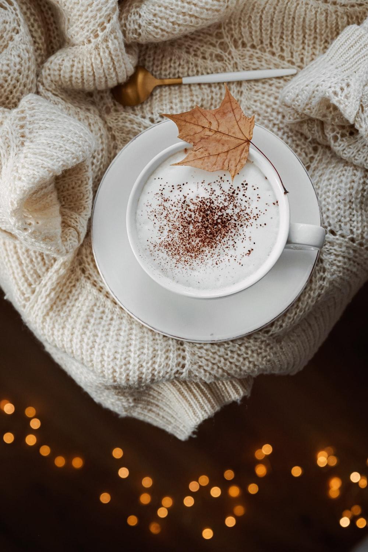 round white ceramic mug on white saucer on sweater