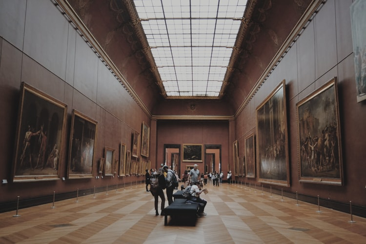 A large room in a museum, the walls are a maroon colour, with very large-format paintings hung on them. People are siting on the benches in the middle and standing around the space.