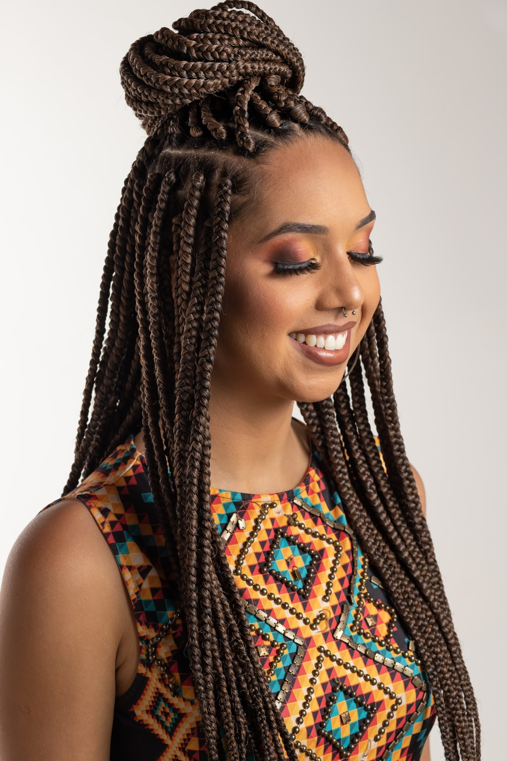 natural hairstyles woman wearing multicolored blouse and braided hair
