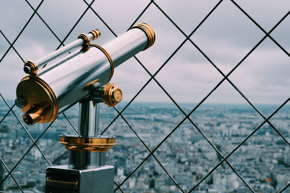 gray and gold telescope behind of cyclone fence