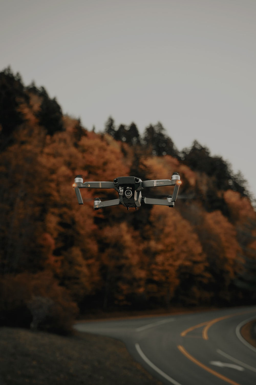 selective-focus of photography of black drone near winding road