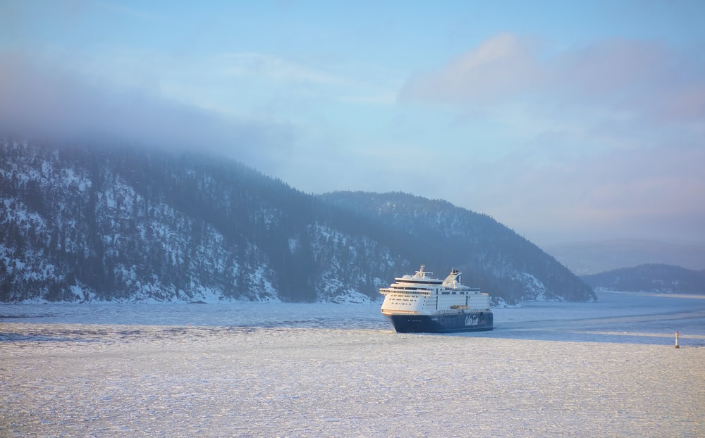 white and black cruise ship in the middle of icy ocean