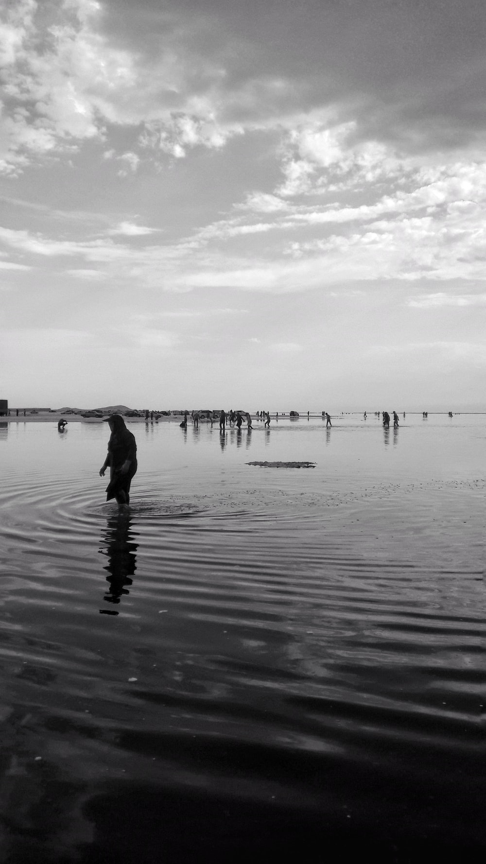 grayscale photo of woman on seashore
