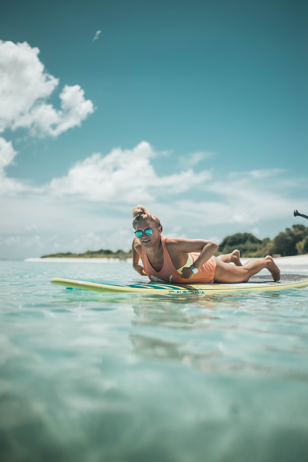 woman prone lying on yellow surfboard during daytime