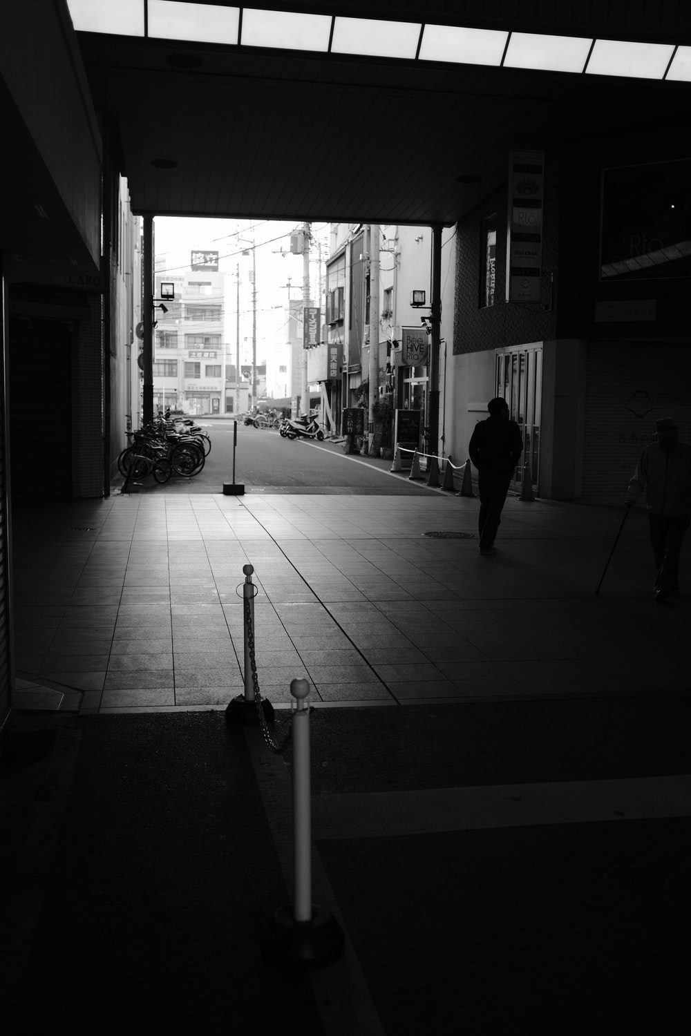 grayscale photography of man standing beside building