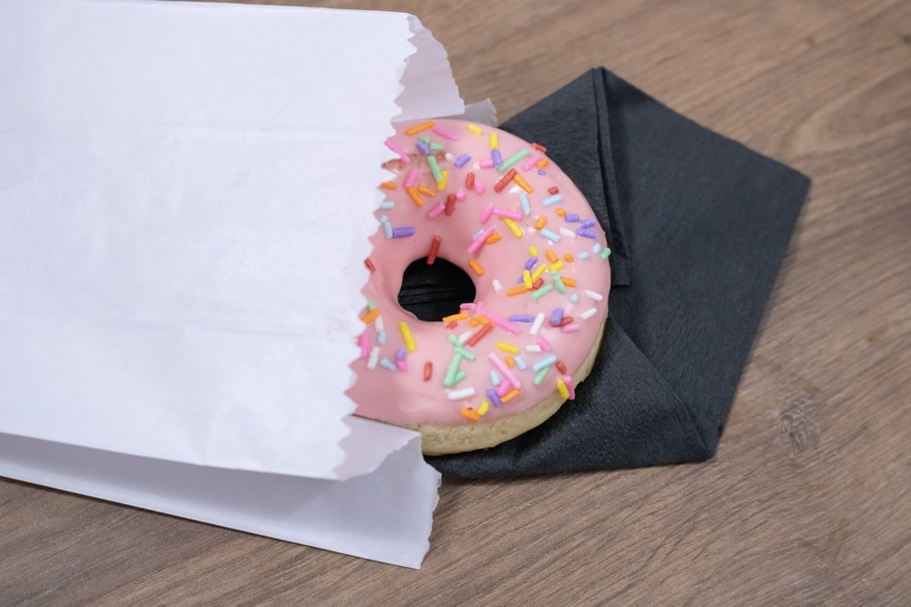 pink donut on white paper bag