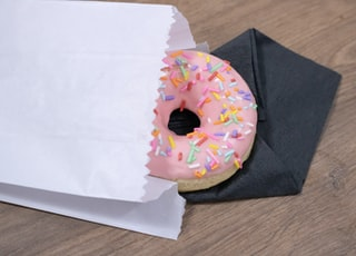 pink donut on white paper bag