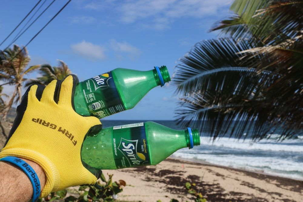 person in yellow glove holding two Sprite plastic bottles