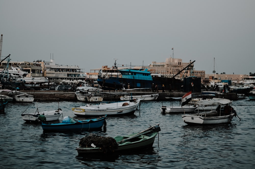 boats and ships in sea under gray sky