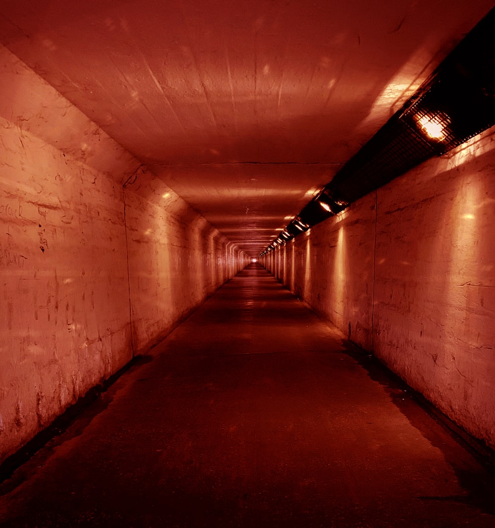 concrete tunnel with red lights