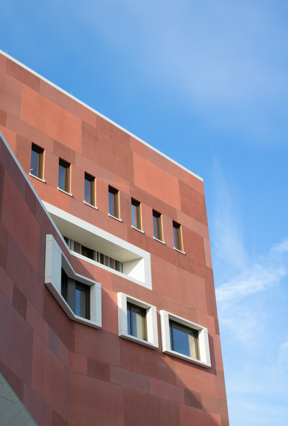 low-angle photography of red concrete building under blue sky