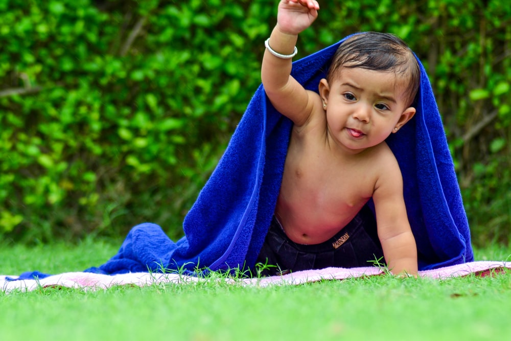 boy lying on blanket covered by blue towel