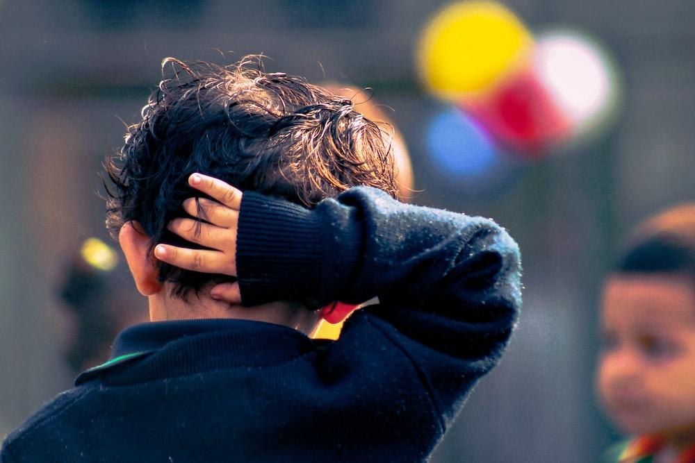 selective focus photography of boy wearing black jacket