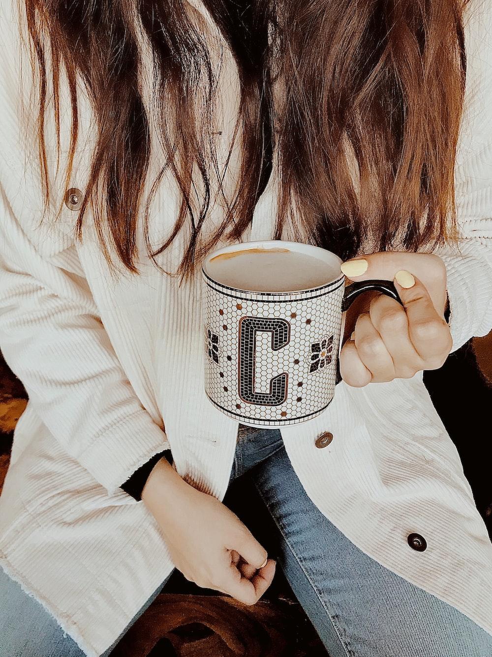 woman holding white and gray ceramic mug