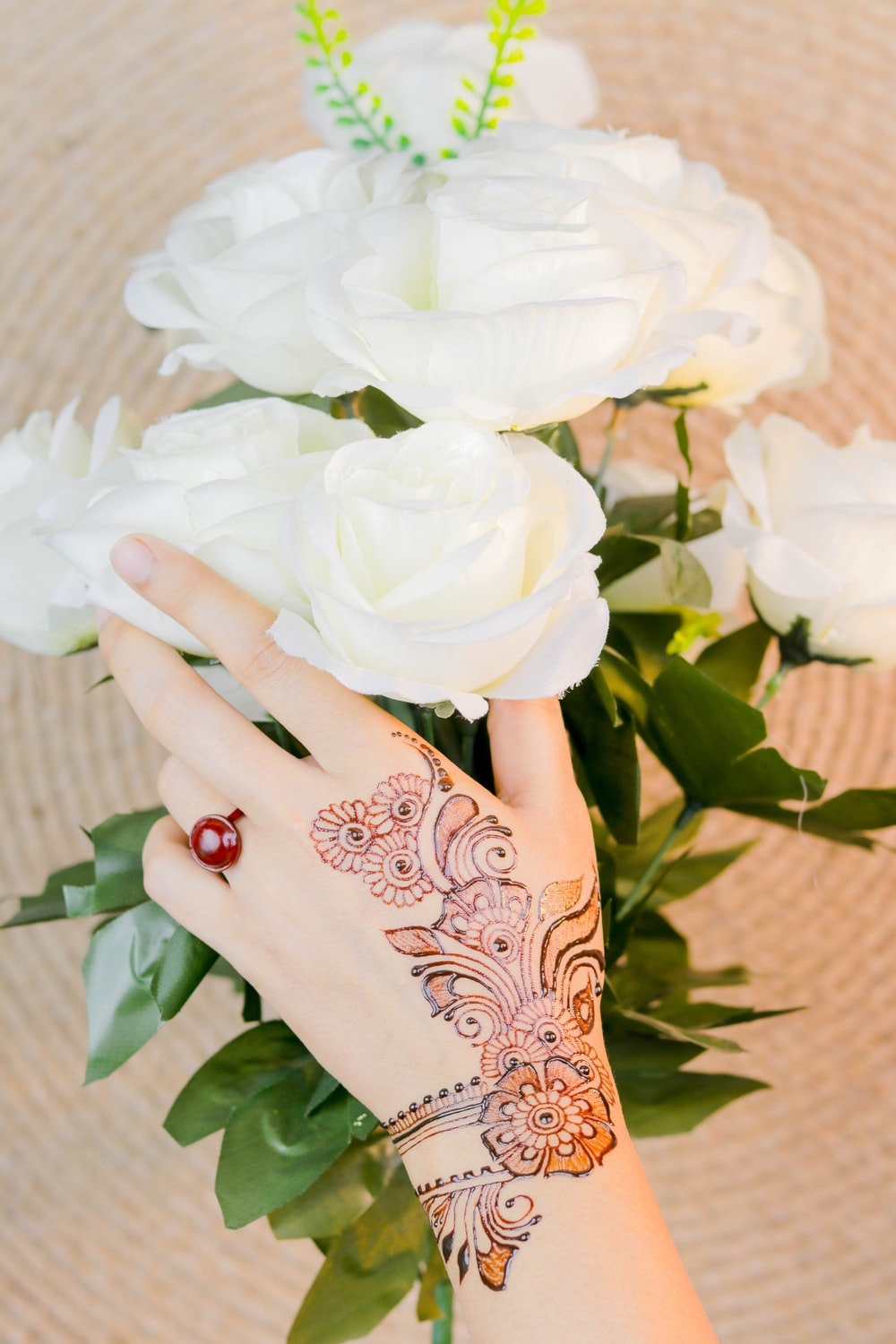 person with brown mehndi tattoo holding white rose flowers