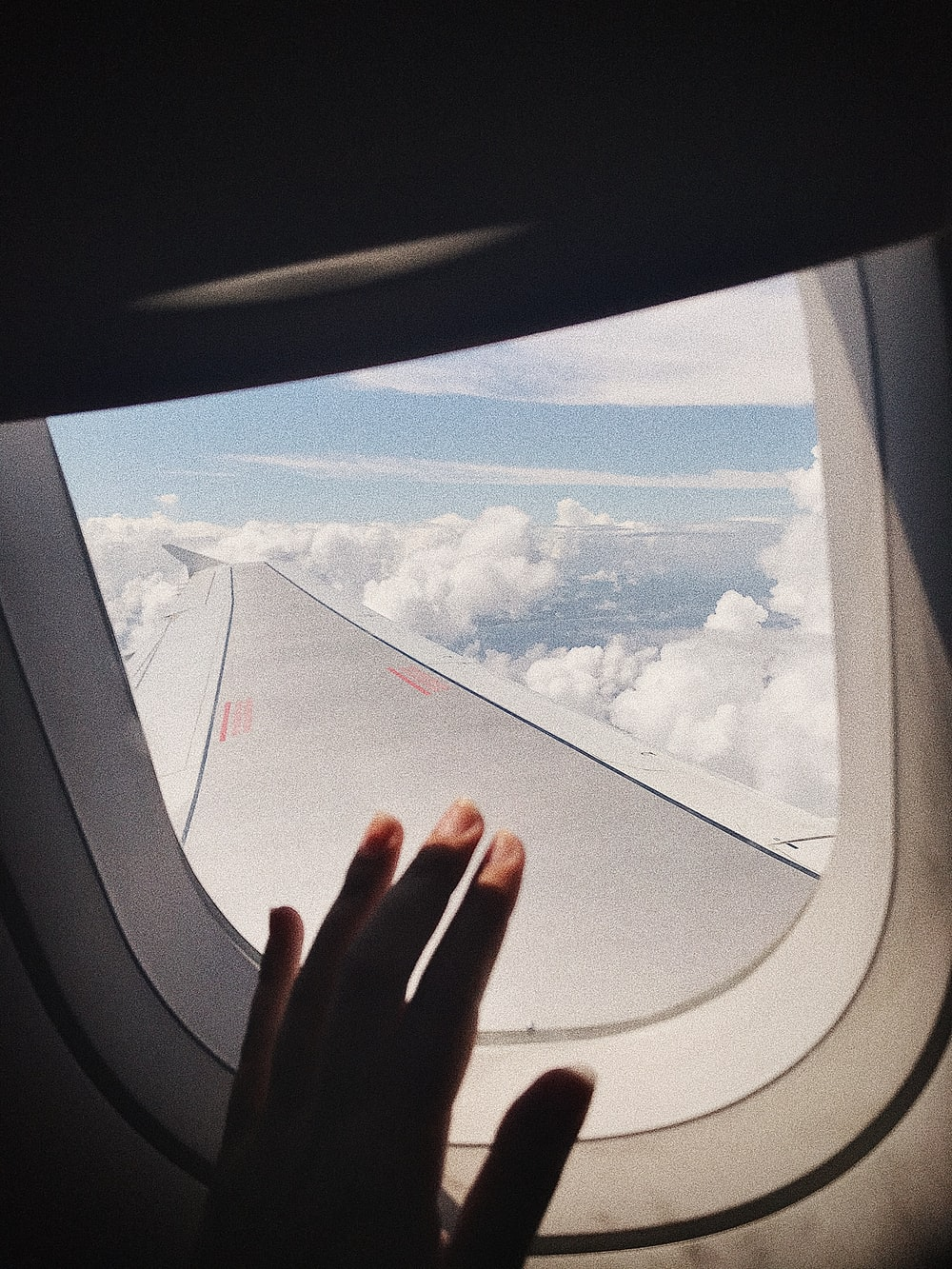 person hand on window of airplane