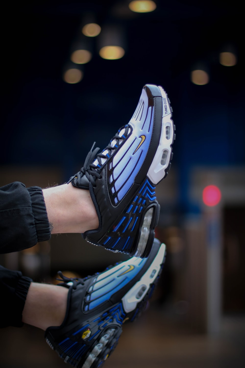person wearing blue-and-white Nike Air Max 95 shoes