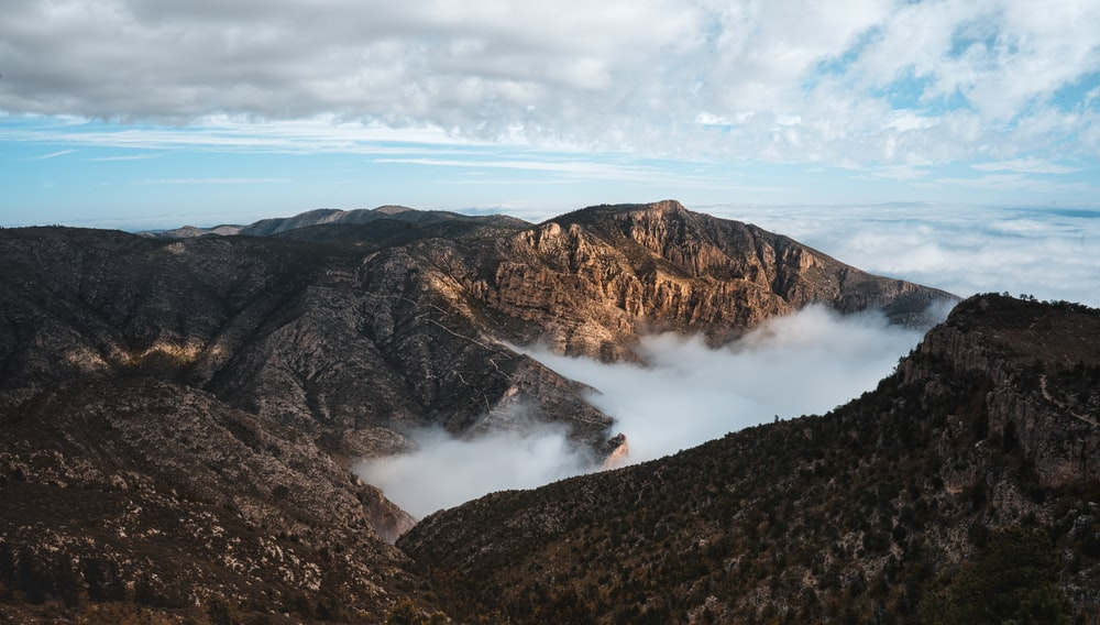 aerial photo of mountains under cloudy sky
