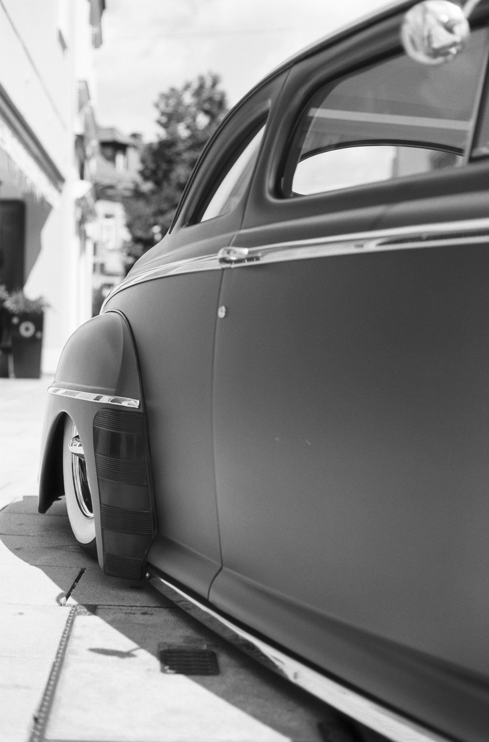 grayscale photo of car parked near building