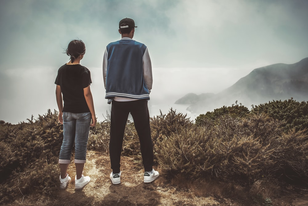 man and woman standing on mountain during day