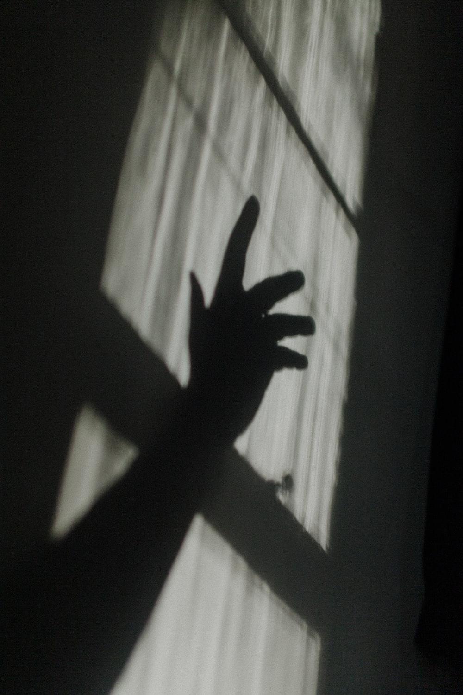 hand shadow on glass window