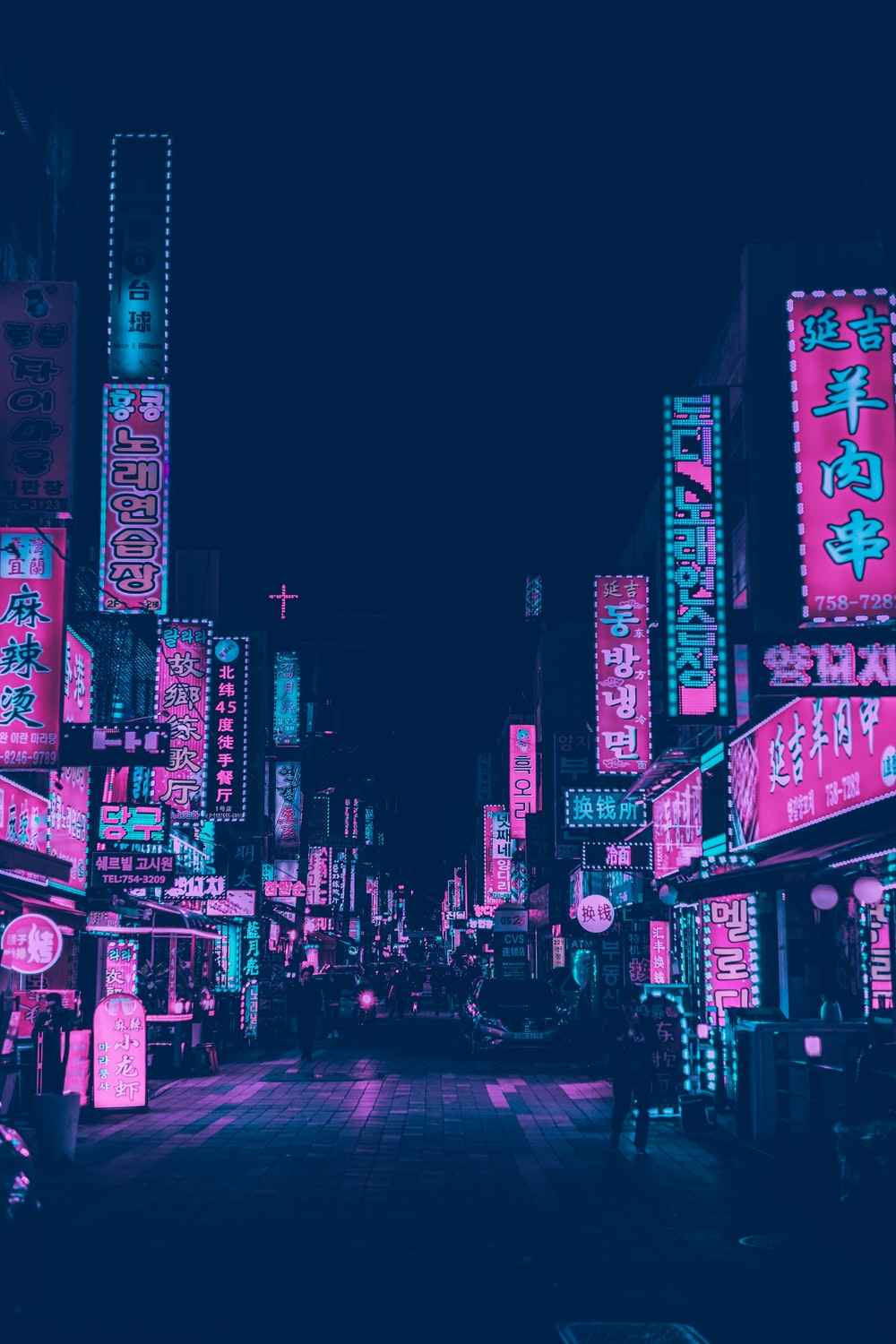 pink and white neon signs of buildings at night