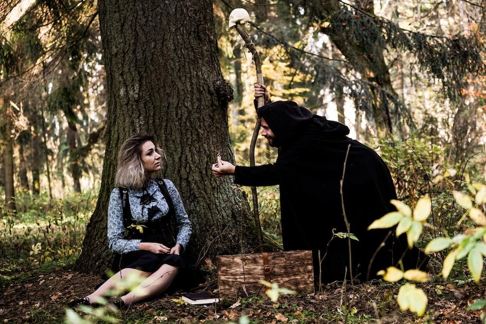 woman sitting beside tree
