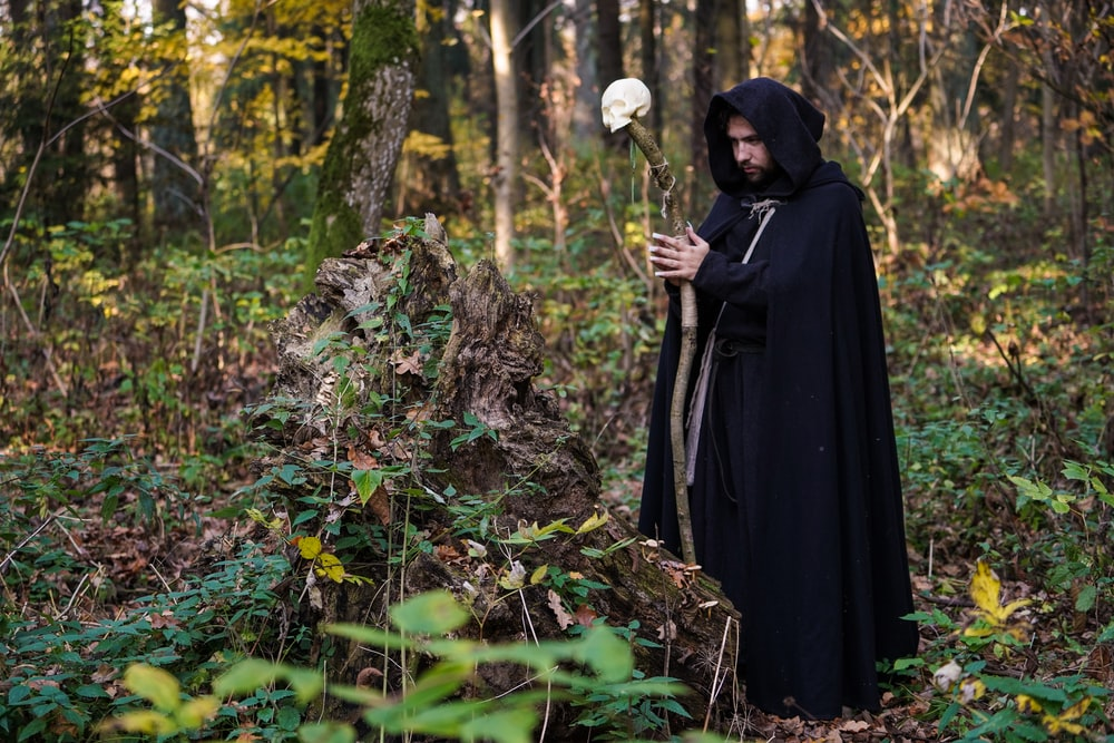 man wearing cloak and holding a wooden cane with white skull ornament