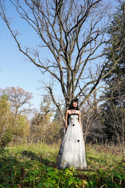 woman wearing dress standing beside bare tree