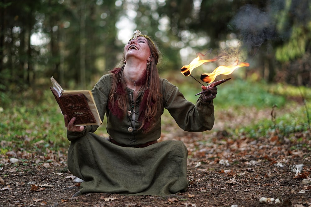 woman holding book and fire