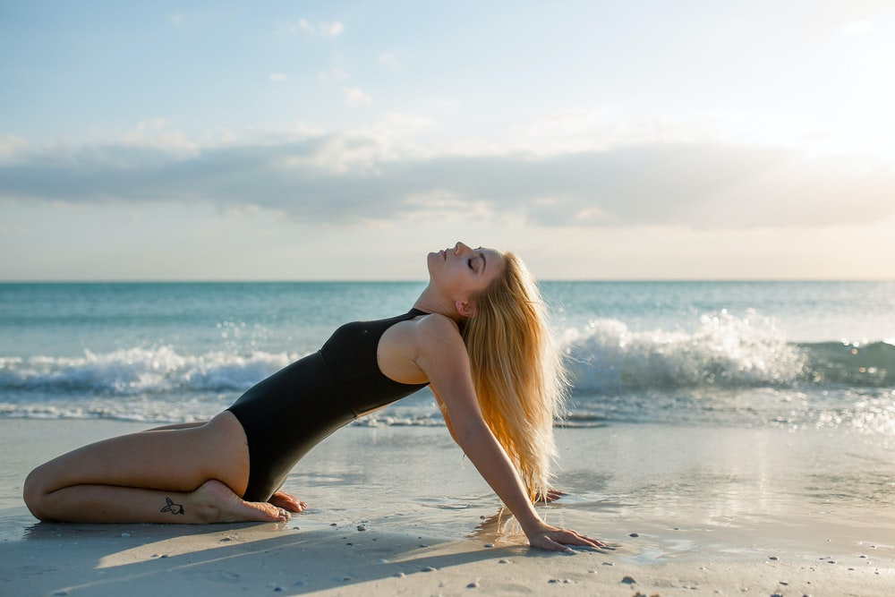 woman wearing black one-piece suit on seashore during daytime
