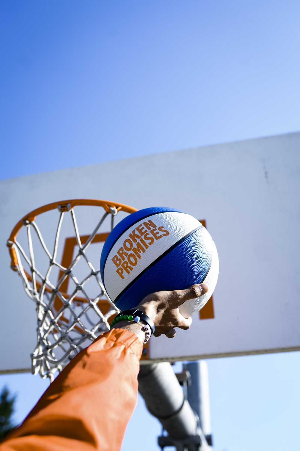 person holding basketball facing towards basketball hoop