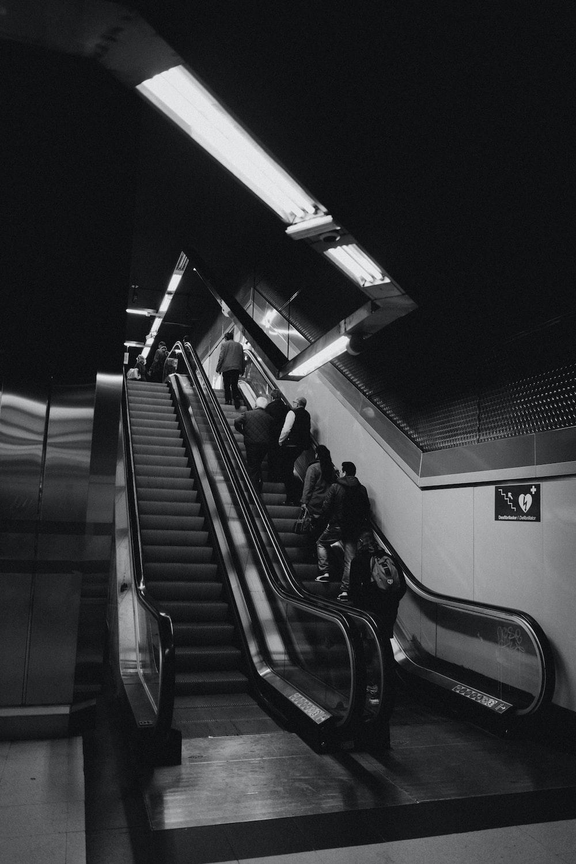 greyscale photo of people standing on subway escalator
