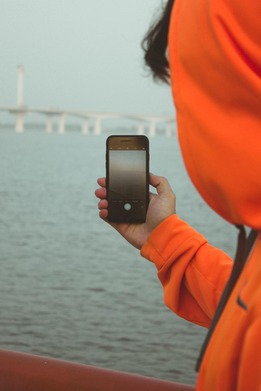 man in hoodie taking photo of bridge during daytime