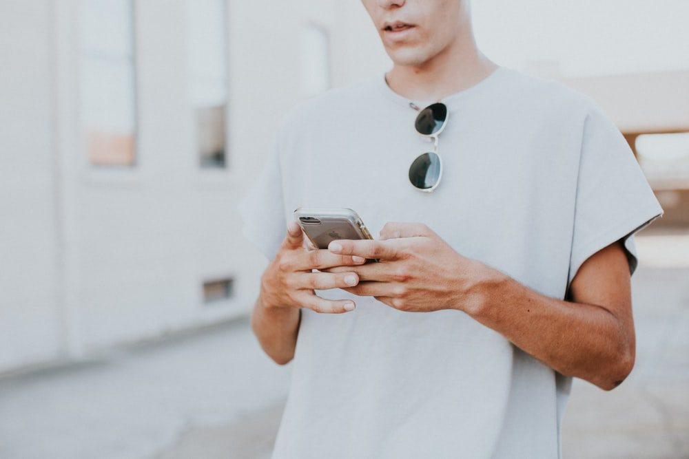 man in white crew-neck top using smartphone outdoors