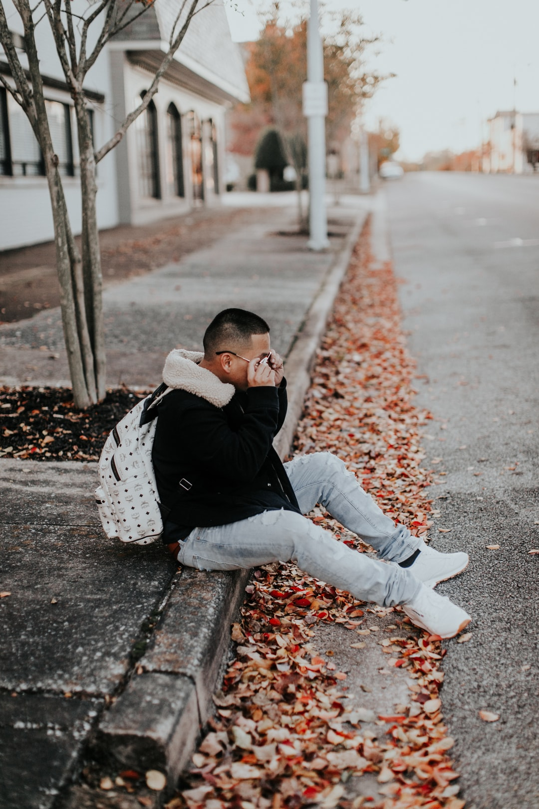 guy sitting on the side of the road in the fall