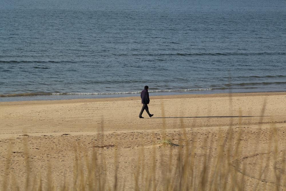 person walking near beach line