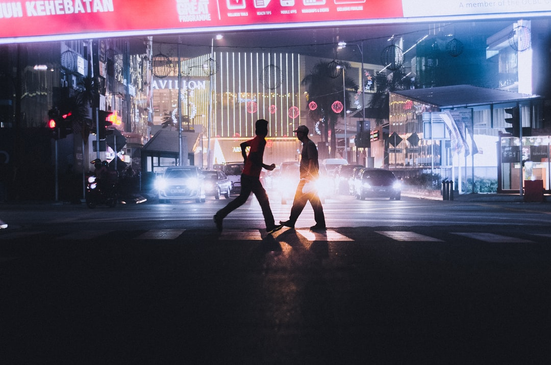 there were two people walking in opposite direction in the middle of the road at Kuala Lumpur