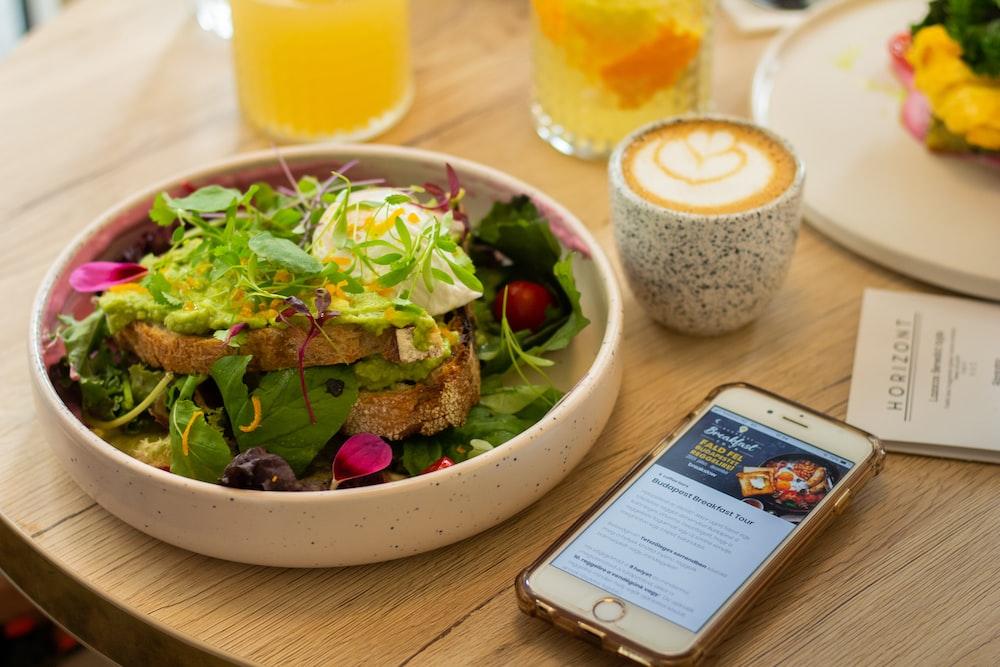 gold iPhone 7 beside vegetable salad on bowl