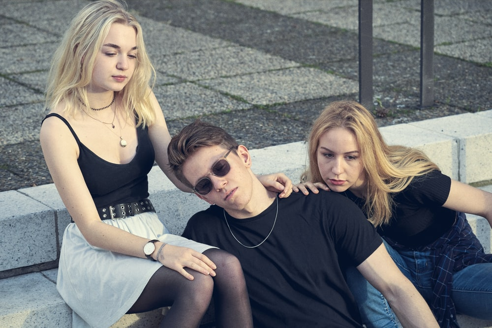 photo shoot of man sits between two women on staircase